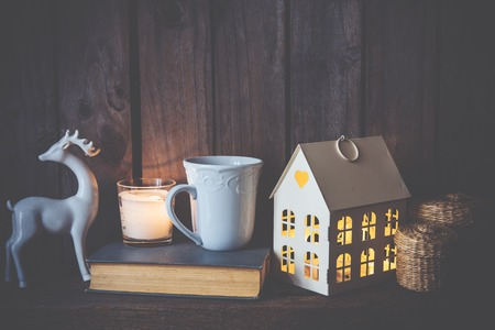 55880931 - cozy vintage home decoration: warm interior night light, books and candles on an old wooden board background.